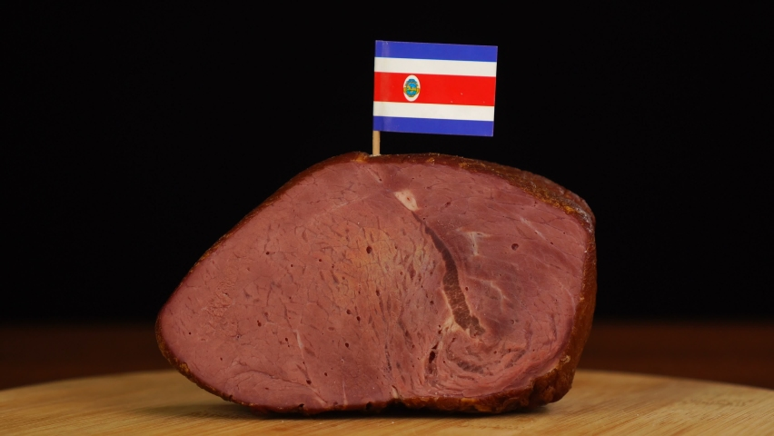 Person placing decorative Costa Rican flag toothpicks into piece of red meat. | Shutterstock HD Video #1070465110