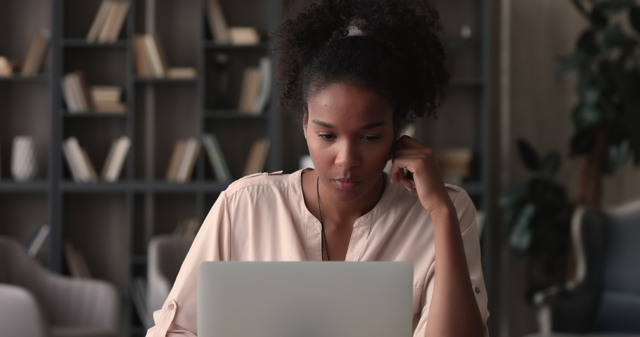 Focused young african ethnic female freelancer businesswoman working on computer at home office, thinking on difficult task or considering problem solution. Smart 25s biracial girl studying distantly. Royalty-Free Stock Footage #1070465992