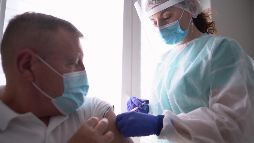 Elderly man getting coronavirus vaccine. Friendly nurse vaccinating an elderly patient against flu, influenza, pneumonia or coronavirus Royalty-Free Stock Footage #1070469859