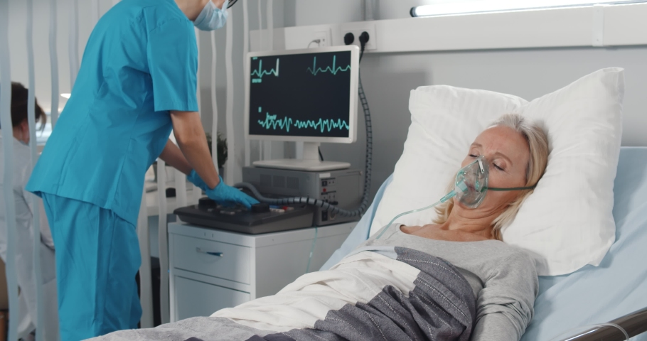 Doctor caring sick patient in hospital checking vital signs on monitor. Portrait of ill senior woman with oxygen mask resting in bed and nurse using computer on background checking physical condition Royalty-Free Stock Footage #1070475631