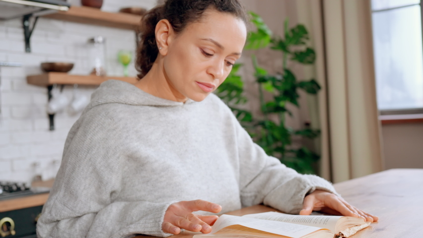adult woman in cozy sweater reading book at home slow motion housewife choose recipe sitting at the table on the kitchen Royalty-Free Stock Footage #1070483542