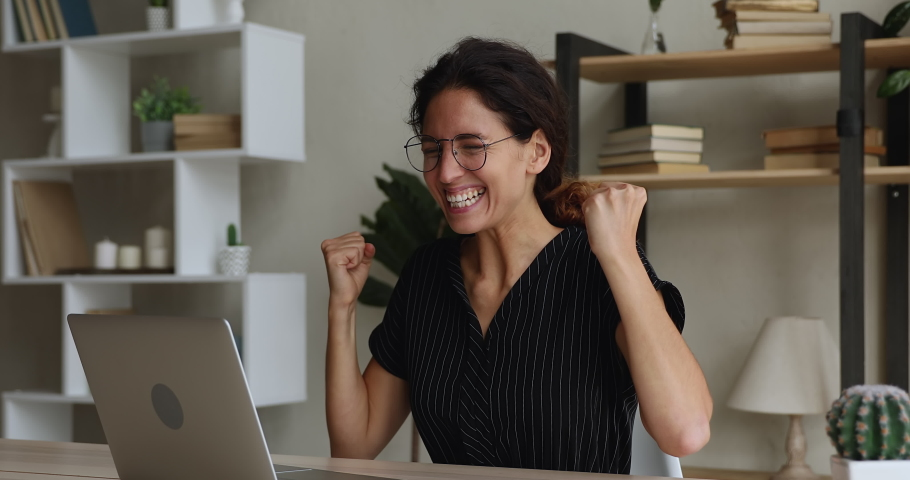 Overjoyed laughing young female employee in eyeglasses looking at computer screen, reading promotion notification, get paid or receive dream job offer, celebrating professional success indoors.