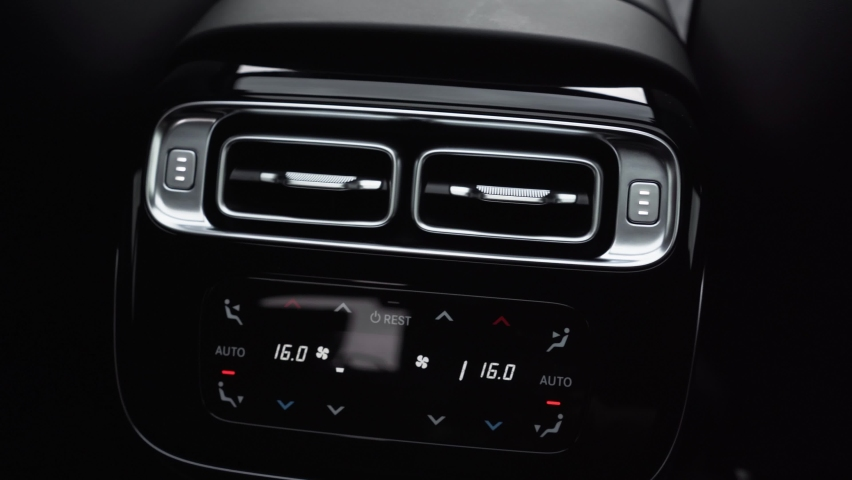 Air duct deflector climate control and control buttons. close-up. Premium car interior with wood trim and LED lighting. Car air deflector for rear passengers Royalty-Free Stock Footage #1070493994