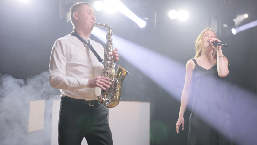 Musical band group of three people playing song, performing on concert musician stage with lights. Singer vocalist girl, saxophonist sax, dj man. Actors dancing, singing Musician playing in band Royalty-Free Stock Footage #1070503087