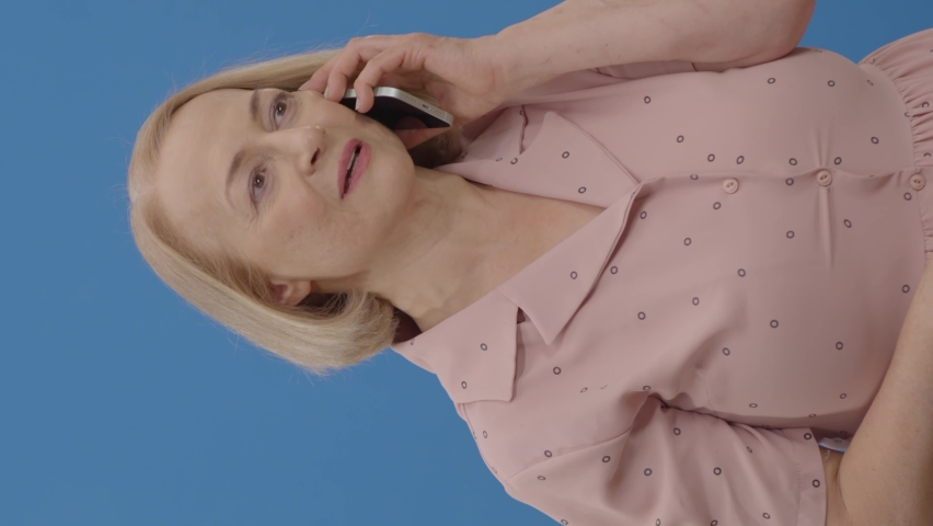 An elderly woman in front of a blue background speaks by mobile phone. Portrait of a fun elderly woman laughing with laughter talking on the phone.Video for the vertical story. Royalty-Free Stock Footage #1070508634