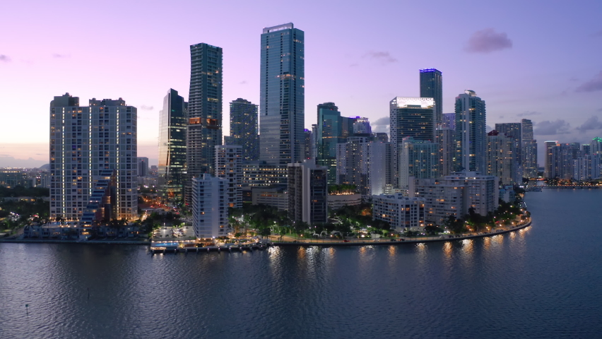 Downtown Miami at pink sunset. Scenic Miami skyline panorama. Aerial view of downtown at night scene. Beautiful urban landscape of coastal bay city at dusk. City lights in purple sunset light. Florida