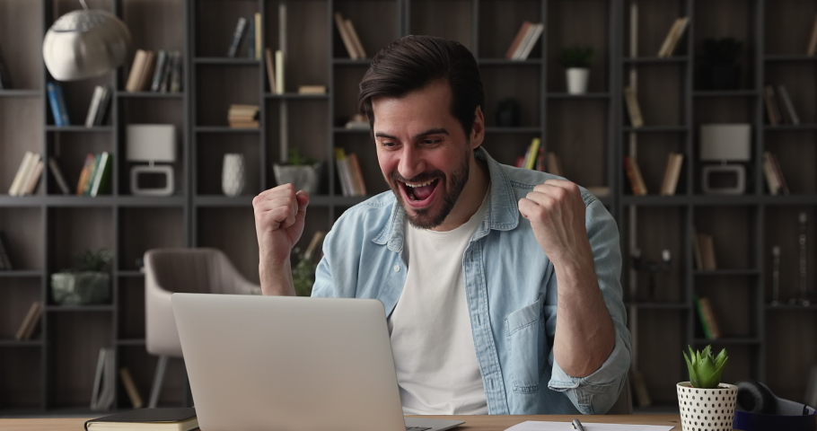 Excited young happy sincere caucasian man looking at laptop screen, feeling amazed by getting email with good news, receiving dream job offer, bank loan mortgage approvement or online lottery win.