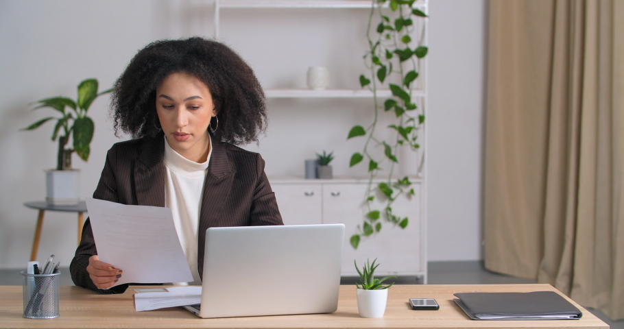 Ethnic student Afro American curly-haired girl sitting at home at table looks at laptop and document studies does paperwork remotely on e-learning during quarantine focused on analyzing project online Royalty-Free Stock Footage #1070524537