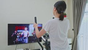 Asian Sport woman workout exercising by watching fitness live or video tutorial TV online on television at home. Casual young Girl using exercise bike follow instruction from trainer during quarantine
