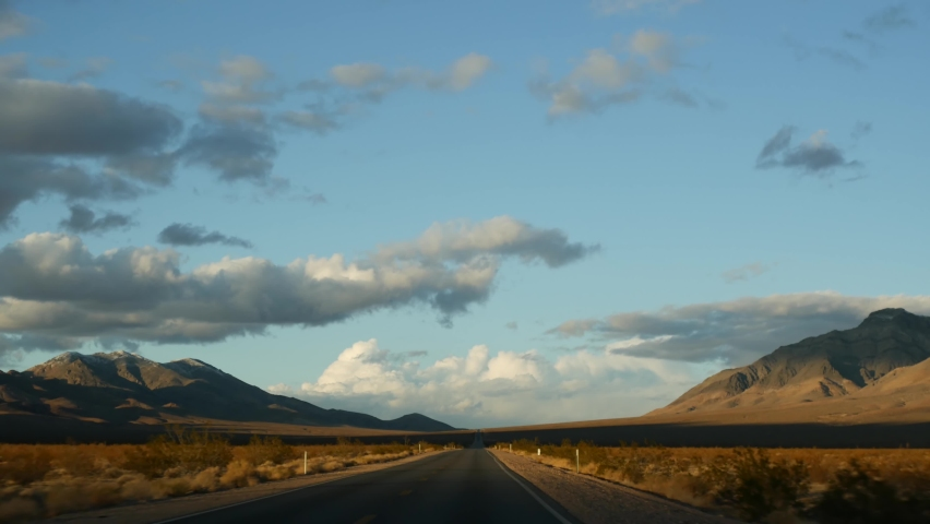Road trip, driving auto from Death Valley to Las Vegas, Nevada USA. Hitchhiking traveling in America. Highway journey, dramatic atmosphere, sunset mountain and Mojave desert wilderness. View from car. | Shutterstock HD Video #1070560579
