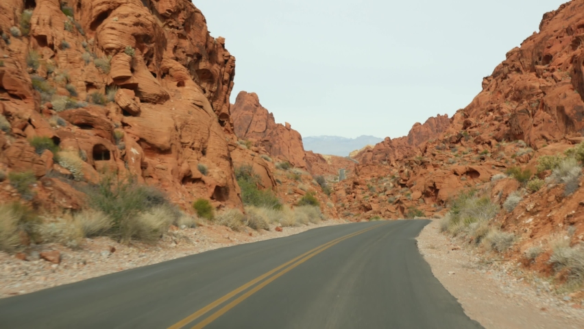 Road trip, driving auto in Valley of Fire, Las Vegas, Nevada, USA. Hitchhiking traveling in America, highway journey. Red alien rock formation, Mojave desert wilderness looks like Mars. View from car. | Shutterstock HD Video #1070560591