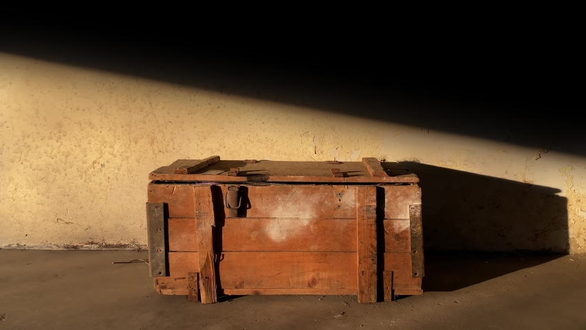 Vertical garage door gate opens to shed light on an old wooden chest against the backdrop of a dirty wall. Treasure hunt documentary | Shutterstock HD Video #1070616451