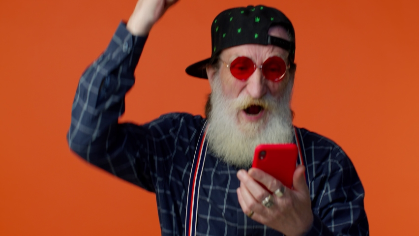 Happy excited joyful elderly bearded gray-haired man use mobile cell phone typing browsing say wow yes, found out great big win news doing winner gesture. Senior old grandfather on orange background | Shutterstock HD Video #1070630149