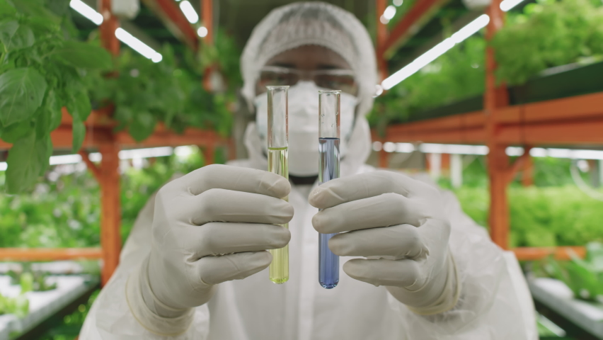 Close up of male agronomic engineer and researcher holding two test tubes with liquid substances of different color sanding at vertical farm indoors | Shutterstock HD Video #1070632501