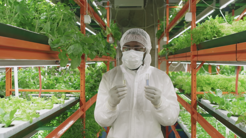 Medium portrait with slowmo of male agronomic researcher wearing protective coveralls, cap, mask and eyeglasses holding two flasks of liquid substances standing in vertical farm looking at camera | Shutterstock HD Video #1070632873