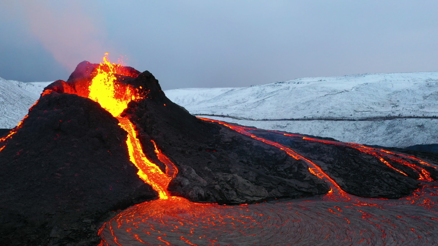 Aerial footage of an icelandic volcano eruptin in 2021 in Reykjanes peninsula, shot at dusk with contrast with snowy mointains and red hot lava