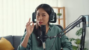 Happy asia girl record a podcast with headphones and microphone look at camera  talk and take a rest in her room. Female podcaster make audio podcast from her home studio, Stay at house concept.