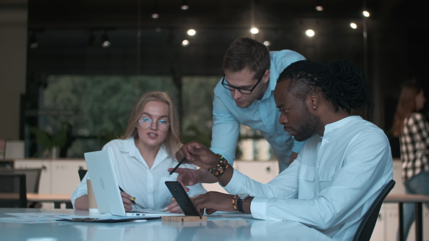 Creative business team, multiethnic group, coworking space. Multiethnic creative business team of three people discussing business plan while sitting at table in modern office Royalty-Free Stock Footage #1070683939