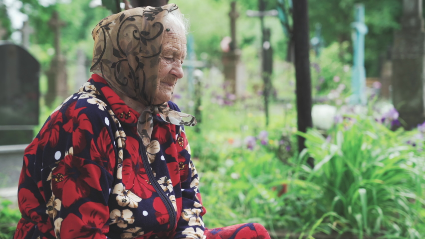 Sad old woman sitting in the cemetery and thinking about life | Shutterstock HD Video #1070706067