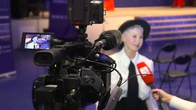 Television camera broadcast interview with business woman speaker in conference hall room Spbd