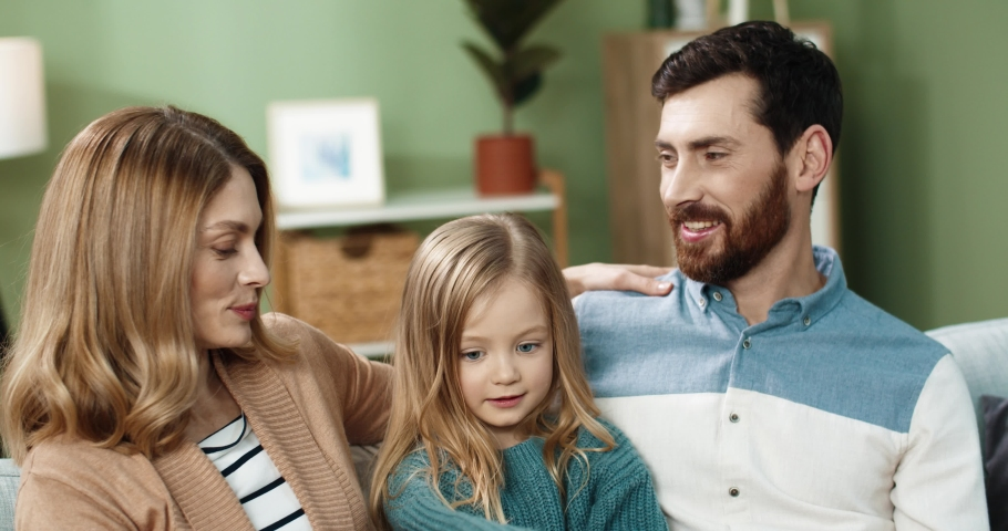Happy Caucasian family sitting at home with little daughter on sofa and talking. Friendly mom dad and baby spend time together on vacation.