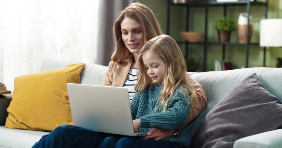 Happy mother and cute little daughter doing interesting tasks together using laptop sitting at home on couch. Royalty-Free Stock Footage #1070737510
