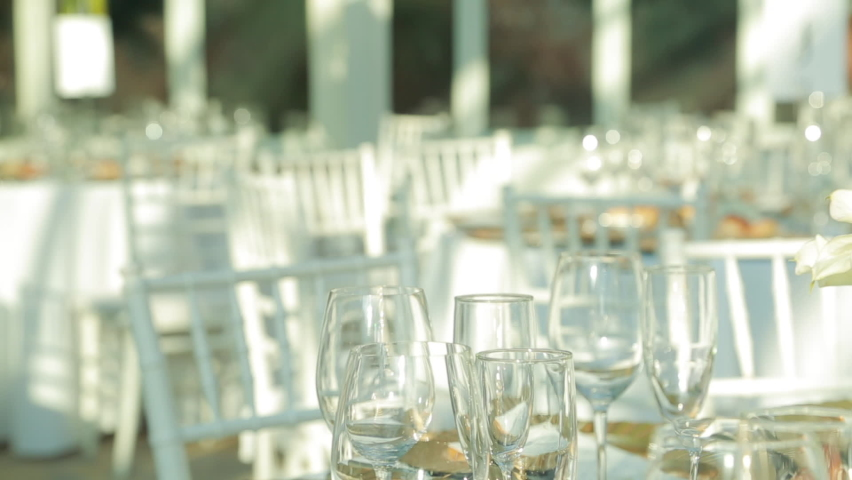 Close-up of a table set with glasses and flower arrangement   Shutterstock HD Video #1070745268