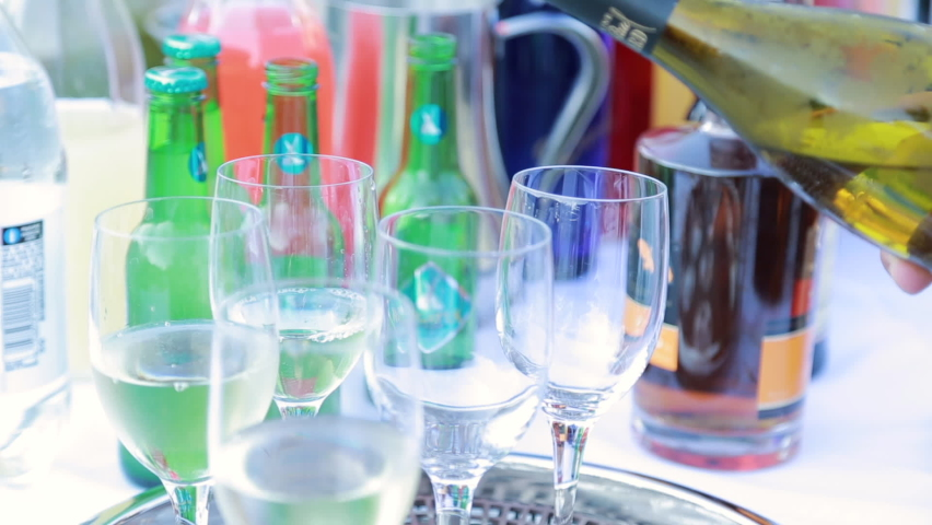 Close-up of wine glasses being filled with white wine   Shutterstock HD Video #1070745280