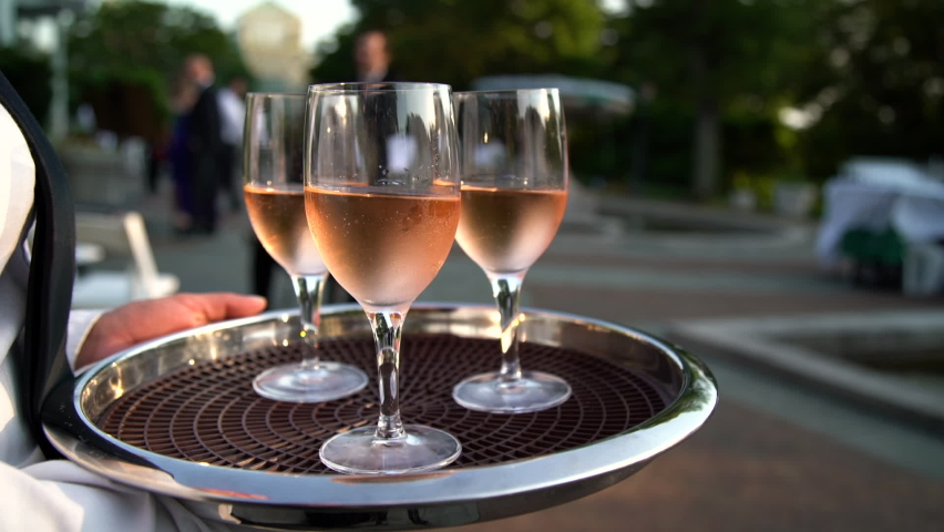 Close-up of a tray with wine glasses at a reception outside on a sunny day   Shutterstock HD Video #1070745301