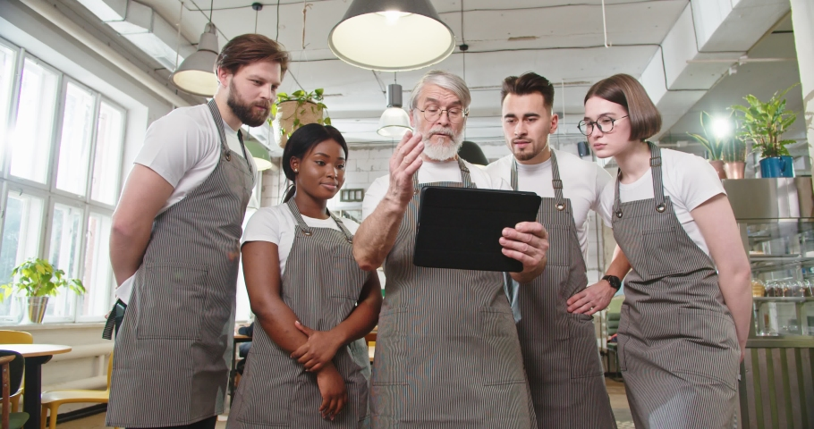 Portrait of busy senior Caucasian male restaurant owner in apron tapping on tablet looking at screen discussing with mixed-race young male and female employees working plan. Business concept Royalty-Free Stock Footage #1070765665