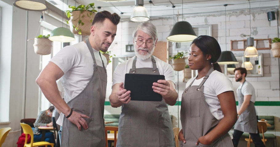 Portrait of serious Caucasian old bearded man in own restaurant in apron tapping on tablet looking at screen discussing with mixed-race young male and female workers colleagues something. Cafe concept Royalty-Free Stock Footage #1070765668