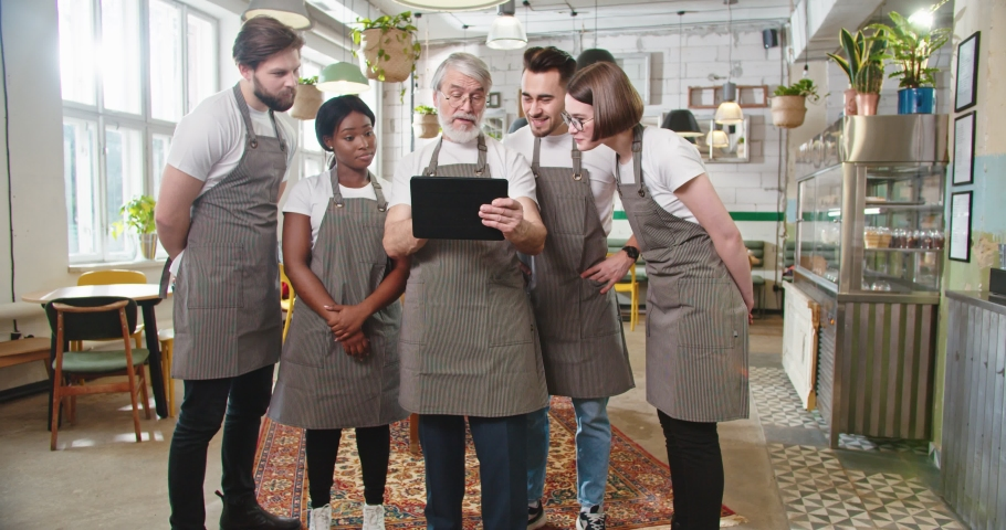 Camera approaching senior Caucasian male manager in apron tapping on tablet surfing internet discussing with mixed-race male and female colleagues working plan. Restaurant concept Royalty-Free Stock Footage #1070765671