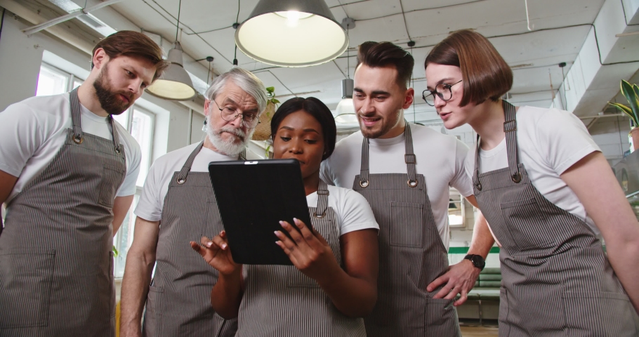 Portrait of young African American pretty female manager in apron tapping on tablet surfing internet discussing with Caucasian male and female colleagues working plan. Restaurant concept Royalty-Free Stock Footage #1070765677
