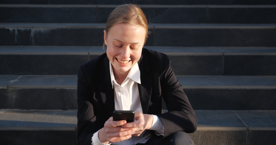 Cute Female Businesswoman is sitting on Stairs near Business Building on warmly Evening. Young Woman holding Smartphone, surfing Internet on the Break. Elegant Woman in Formal Suit. Business Portrait.