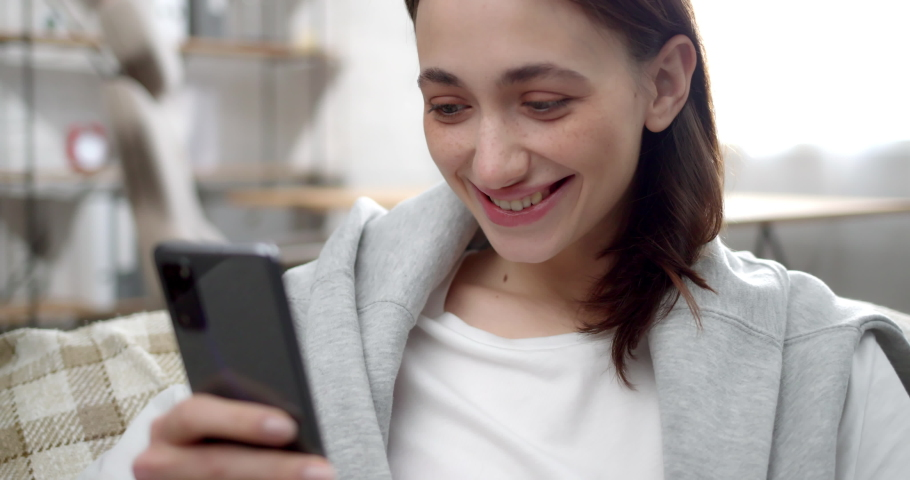 Pretty Young Girl with Freckles sends emotions in Chat using Mobile Phone. Positive Woman sitting on comfortable couch at Home enjoying Browsing on Social Networks. Looking at Phone screen with smile. Royalty-Free Stock Footage #1070774905