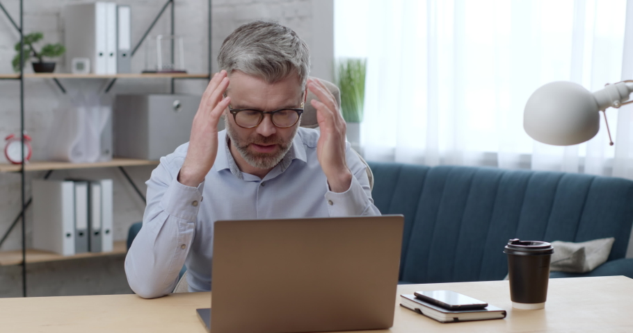 Frustrated Man in Eyeglasses feeling Worried about Financial problems. Stressed Freelancer touching his head while sitting at Workplace thinking about Money, Budget loss, or Unsaved Files. Bankruptcy.