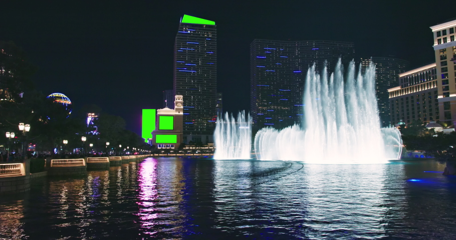 Las Vegas fountains. Modern skyscraper hotel buildings with green screens for business advertisement. Night scene the Strip night life with casinos and adult attractions. Urban illumination footage 4K | Shutterstock HD Video #1070775151