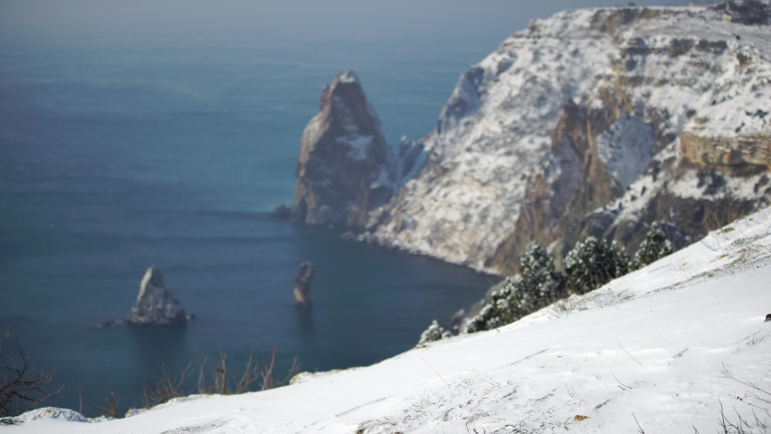 Snow covered rocky cliffs over sea. Winter landscape over the sea bay. Juniper tree under snow. Concept of winter holidays, travel and recreation. Cape Fiolent in Balaklava, Sevastopol, Crimea | Shutterstock HD Video #1070781043