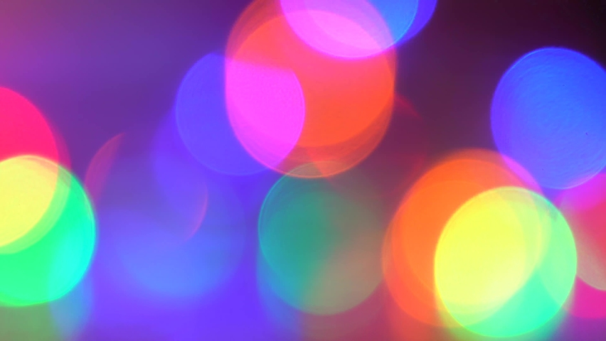 Bright vivid 4k stock video footage of blinking holiday bright bokeh lights of different colors shining in darkness. Red, blue, purple, pink, green, orange colors changing quickly | Shutterstock HD Video #1070781151
