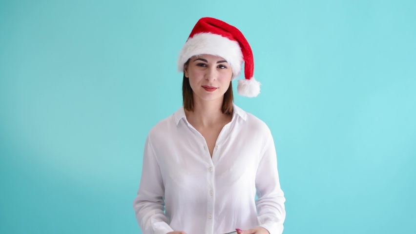 Beautiful caucasian woman wearing white shirt and santa hat smiles and plays with money in her hands. 4k resolution video. Blue background. Christmas lottery win theme. | Shutterstock HD Video #1070782732