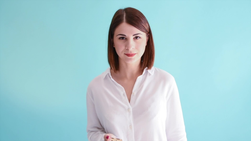 Beautiful caucasian woman in white shirt holds two small different wooden models of house in her hands. She picks one and holds it forward. Blue background. Real estate theme. | Shutterstock HD Video #1070782765