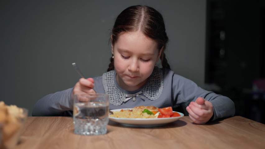 Little beautiful girl is eating in the kitchen. She sits on a chair at the table. The child eats pasta with a fresh salad of tomato, pepper and round cheese. 4K | Shutterstock HD Video #1070784949