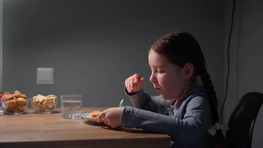 Little beautiful girl is eating in the kitchen. She sits on a chair at the table. The child eats pasta with a fresh salad of tomato, pepper and round cheese and drink water. 4K | Shutterstock HD Video #1070784952