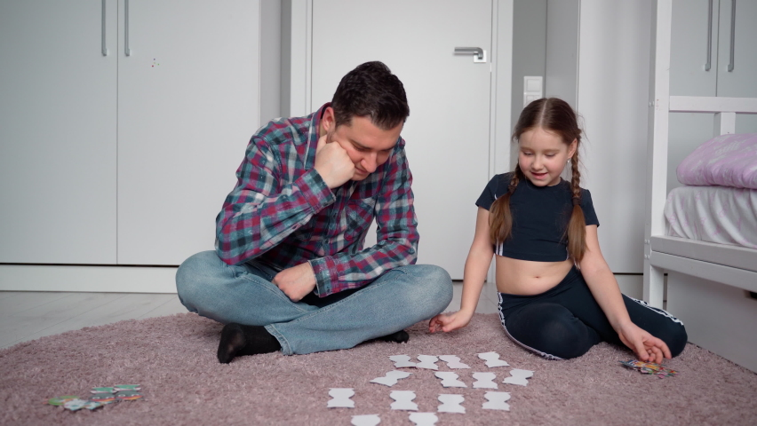 Father and daughter are sitting on the floor in a bright children's room and playing a board game find a match. They hug after playing together. Positive emotions from father's day. Joint pastime. 4K	 | Shutterstock HD Video #1070784955