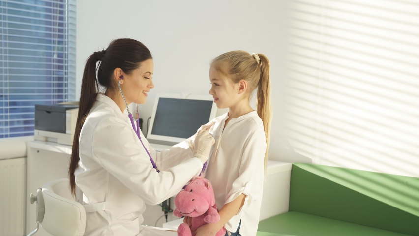 Pediatrician examines child, applies stethoscope to child's body, listens to the heart and lungs of teenage girl. awesome child in a hospital room. | Shutterstock HD Video #1070785330