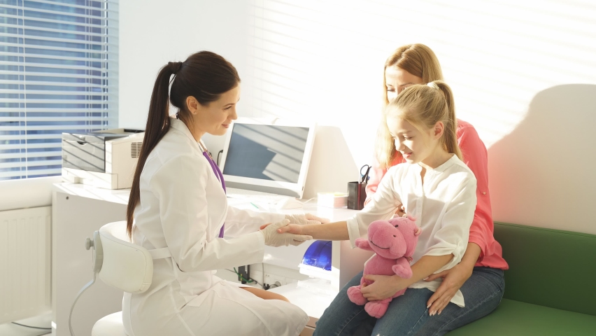 Female pediatrician welcome small kid patient and her mother at medical check up appointment, children medical health care concept. | Shutterstock HD Video #1070785333