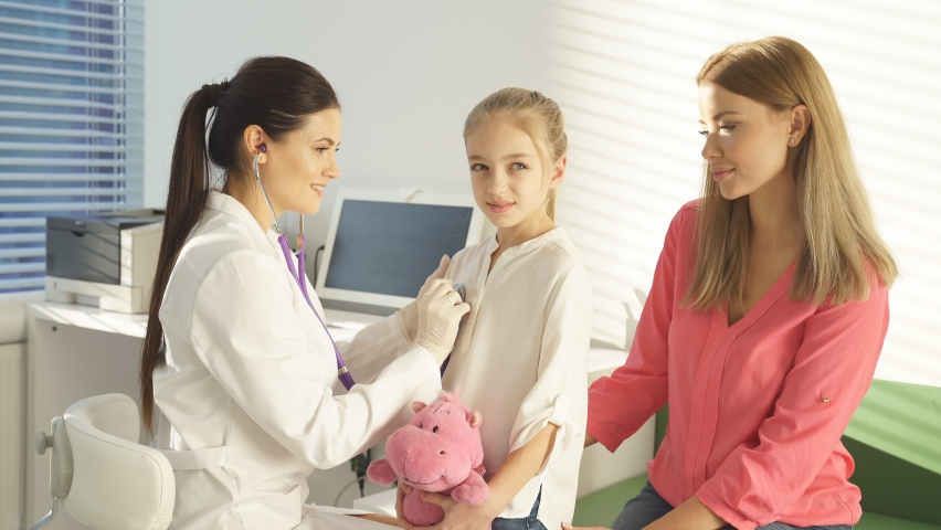 Female doctor or pediatrician with stethoscope listening to heartbeat girl's patient on medical exam at clinic. Kid girl on medical examination checkup. | Shutterstock HD Video #1070785339