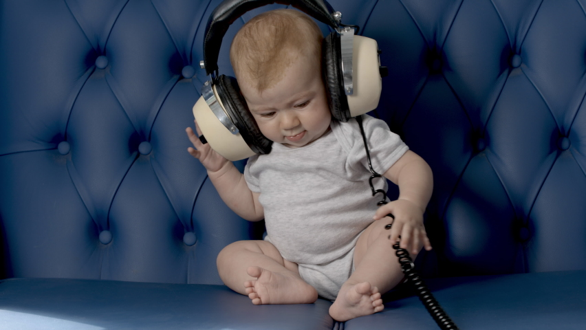 Adorable small baby girl with large vintage headphones on blue leather sofa looping back and forwards | Shutterstock HD Video #1070788765