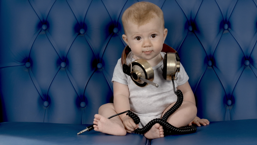 Adorable small baby girl with large vintage headphones on blue leather sofa | Shutterstock HD Video #1070788774