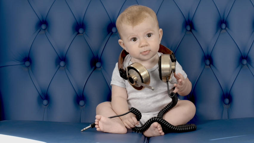 Adorable small baby girl with large vintage headphones on blue leather sofa | Shutterstock HD Video #1070788780
